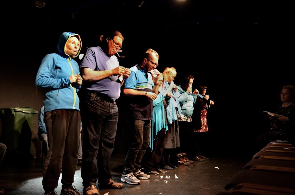 Esiintyjät seisoo rivissä yleisöön päin samalla, kun syö papereita