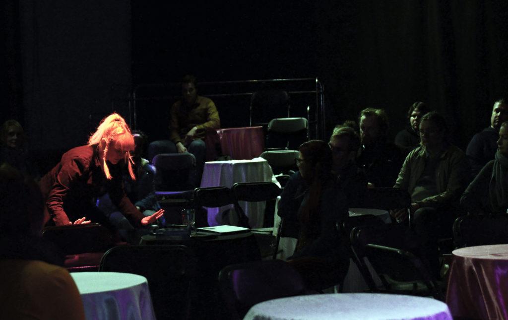 Pöydissä istuu katsojia, jotka katsoo vasemmalla missä Metsälintu Pahkin tekee esitystään