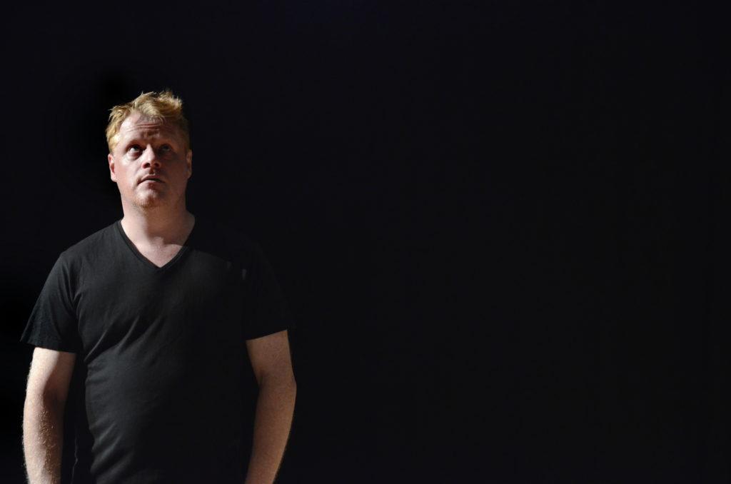 Tim Saarinen seisoo kuvan vasemmalla puolella, jossa muut kohdat on täysin mustaa taustaa. Katsoo ylöspäin kysyvänä