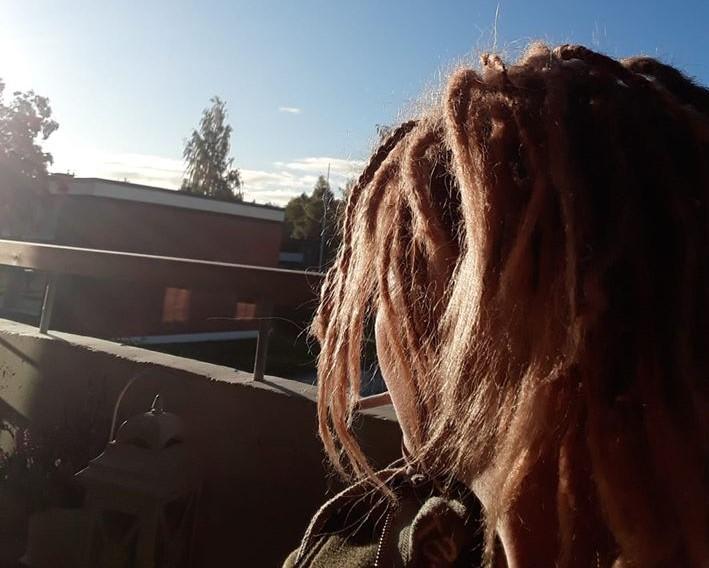 nainen katsoo kohti aurinkoa