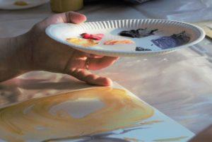 kädessä on pahvilautanen, jossa on erivärisiä maaleja. Pöydällä on keltaisella maalilla maalattu keskeneräinen maalaus