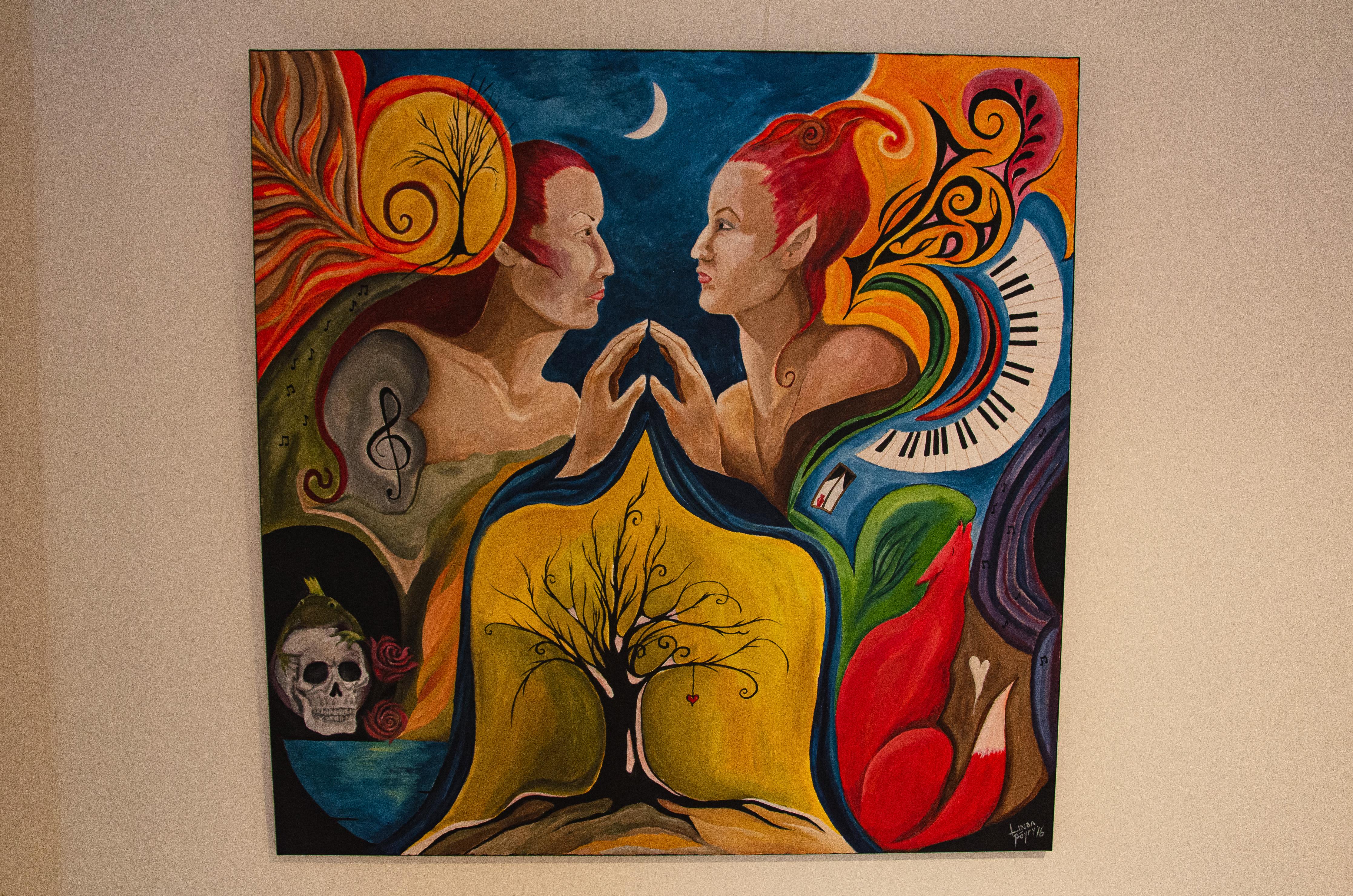 Kaksi henkilöä katsoo toisiaan. Ympärillä on värikkäästi erilaisia objekteja, kuten pianon koskettimet, kallo, kettu, kuu ja nuotti. Kuvan alapuolella on vanha lehdetön puu