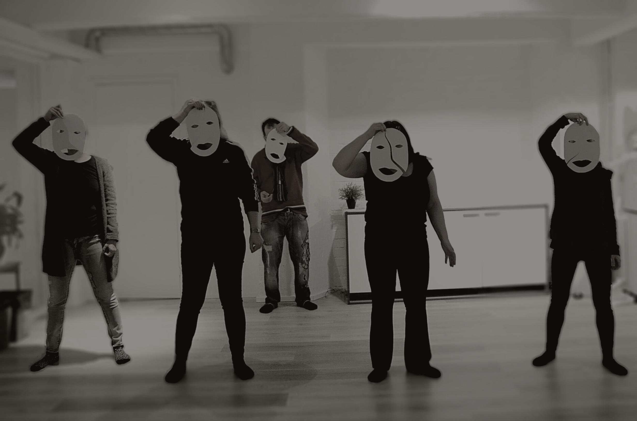 Viisi ihmistä pitää naamareita kasvojensa edessä tummasti valaistussa huoneessa